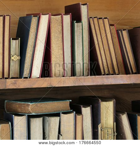vintage books on wooden shelf.
