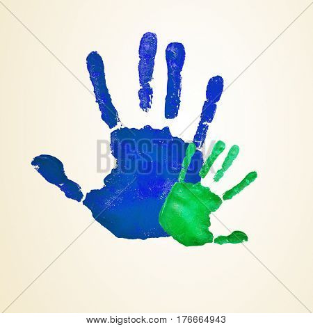 a blue handprint of an adult and a green infant handprint, depicting the idea of family, or the relationship of a father or mother and his or her son or daughter