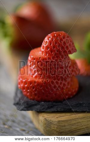 closeup of a sliced ripe strawberry on a wooden chopping board and some whole strawberries in the background, on a rustic wooden table