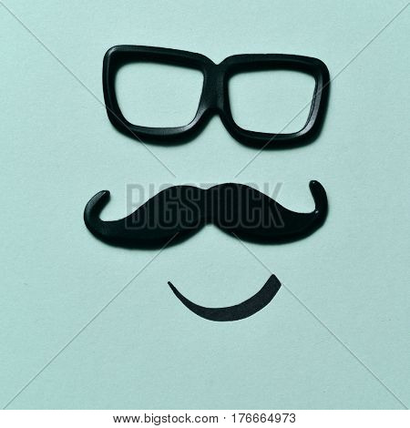 a pair of black plastic-rimmed eyeglasses and a mustache depicting a man face, on a blue background