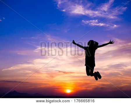 Silhouette of woman jumping Happiest moments at sunset and feeling free.