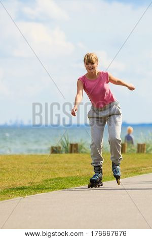Relax leisure sport fitness exercise concept. Girl skating alone on seafront. Young casual lady riding on roller blades.