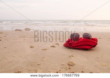 Sunglasses with red fabric on the sand