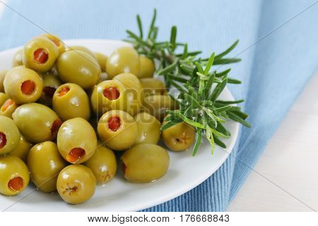 plate of green olives stuffed with red pepper on blue place mat - close up