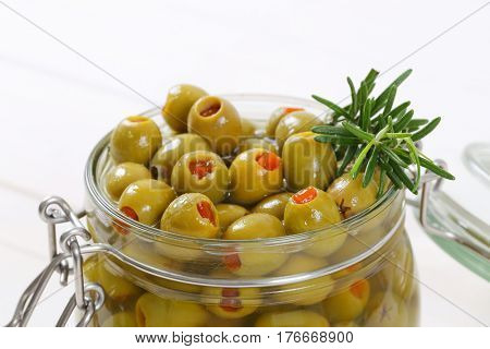 jar of green olives stuffed with red pepper - close up