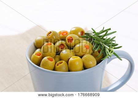 cup of green olives stuffed with red pepper - close up
