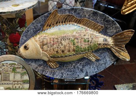 TIBERIAS ISRAEL - FEBRUARY 26 2017: Dish with Saint Peter's fish. Fish is decorated with a picture of the houses of Jerusalem ceramics