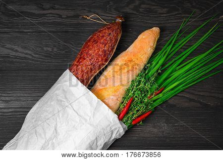 A grocery shopping set in a paper bag at the grocery store for sandwiches. Smoked sausage bread baguette green onion thyme red pepper. Dark brown wooden background.