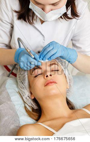 Dermabrasion girl's forehead. Machine cosmetology. Spa. Facial Rejuvenation. Mechanical peeling skin.
