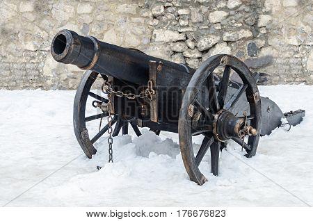 Old black gun in ancient castle of Mukacheve Ukraine winter time