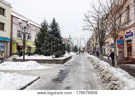 Mukachevo Ukraine - January 31 2017: Dukhnovicha street in center of Mukachevo. Dirty snow on a roadside nasty winter day.