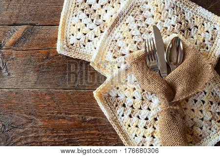 A top view image of silverware wrapped in burlap canvas and placed on crochet place mats.