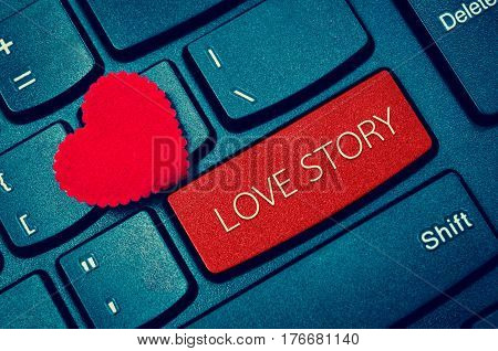 Computer keyboard and red heart with word LOVE STORY.