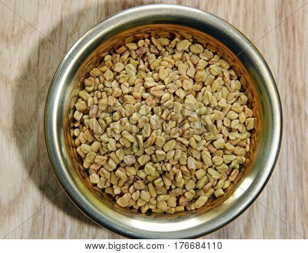 A close up of a bowl of Fenugreek seeds. Top view.