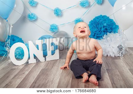 Portrait of crying screaming unhappy Caucasian baby boy in dark pants on his first birthday with letters one and balloons sitting on wooden floor in studio