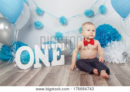 Portrait of adorable Caucasian baby boy with blue eyes in dark pants and red bow tie celebrating his first birthday with letters one and balloons sitting on wooden floor in studio