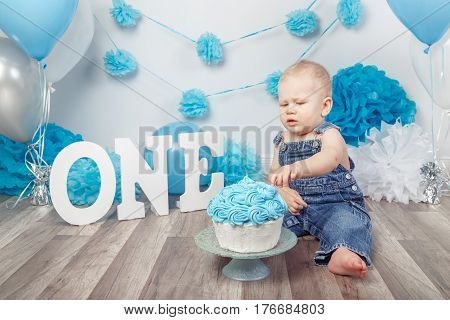 Portrait of cute adorable blond Caucasian baby boy with blue eyes in jeans overall celebrating his first birthday with gourmet cake letters one and balloons cake smash in studio