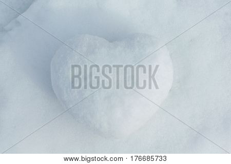 In winter the white snow lies cobbled together a snowball in the shape of a heart. On the street the day and the sun is shining. Cold and frosty. Can be used as a gift a surprise.