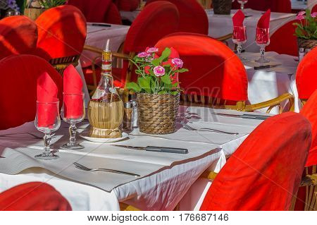 Romantic table setting with olive oil balsamic vinegar and flowers at an Italian open air street restaurant in the Old Town Nice Vielle Ville in the South of France