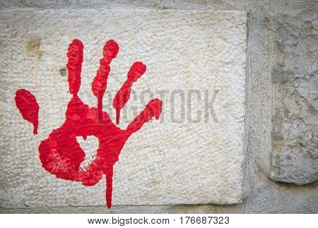 Bloody palm print on a stone wall