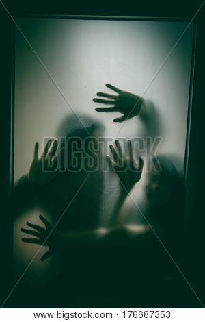 Horror hands. Silhouettes through glass