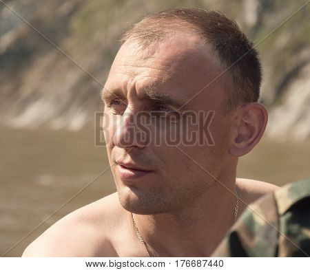 Portrait of strong Man near forest river, telephoto