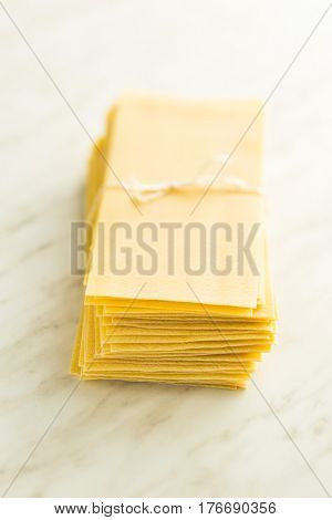 Raw lasagne sheets on kitchen table.