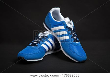 Varna Bulgaria - MARCH 12 2017 : ADIDAS V RACER running shoe on dark background. Product shot. Adidas is a German corporation that manufactures sports shoes clothing and accessories