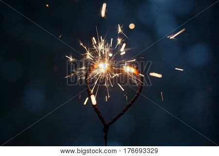 Heart shape sparkler burning in the dark