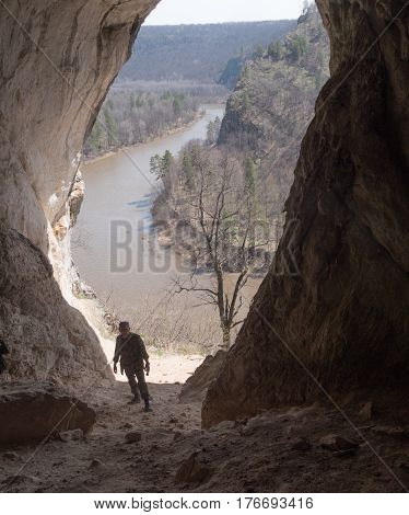 Adult man in military uniform in cave near rock river, wide angle