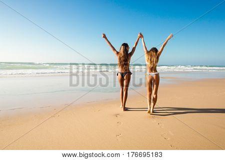 Beautiful girls in bikin walking on the beach
