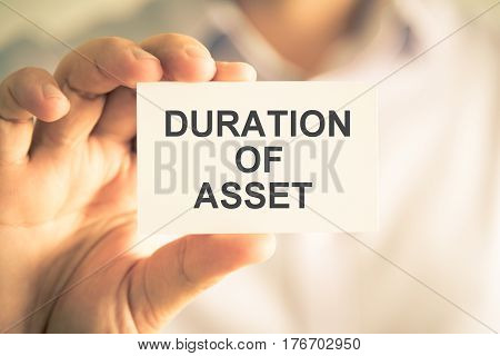 Businessman Holding Duration Of Asset Message Card
