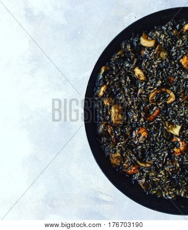 Black Rice Paella with squid ink in pan top view on white textured background