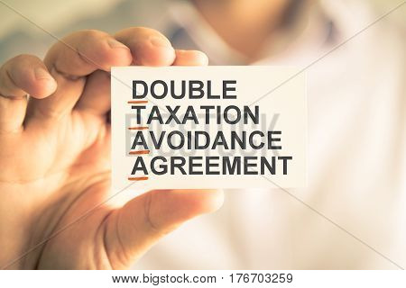 Businessman Holding Card With Dtaa Double Taxation Avoidance Agreement Acronym Text