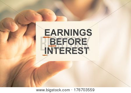Businessman Holding Card With Ebi Earnings Before Interest Acronym Text