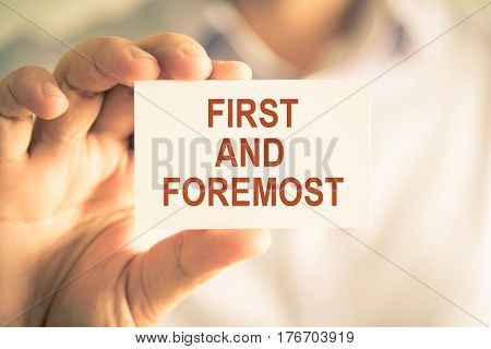Businessman Holding First And Foremost Message Card