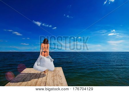 young beautiful woman taking off sweater and going to ocean on wooden pier