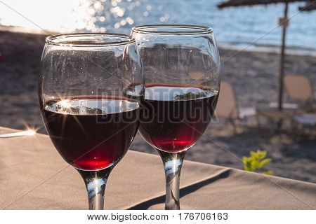 Two glasses with red wine with sun reflection, sea, sunset on beach at the background. Summertime vacation concept