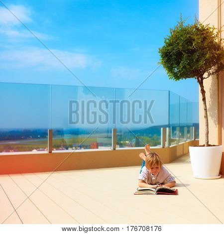 young boy relaxing on roof top terrace summertime