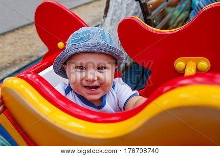 Happy little boy is swinging on see-saw