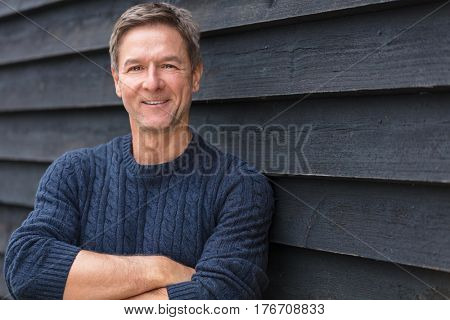 Portrait shot of an attractive, successful and happy middle aged man male arms folded outside wearing a blue sweater