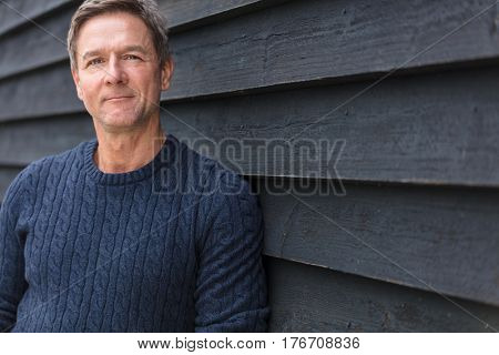 Portrait shot of an attractive, successful and happy middle aged man male outside wearing a blue sweater