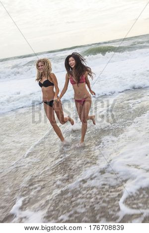 Young women or girls in bikinis running in the sea waves on a beach