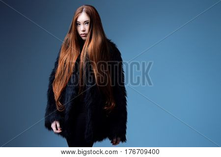Fashion shot. Portrait of a fashionable model with beautiful long hair posing at studio in black fur coat.