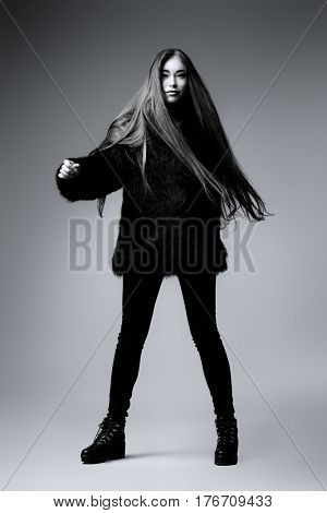 Fashion shot. Black-and-white portrait of a fashionable model with beautiful long hair posing at studio in black fur coat.