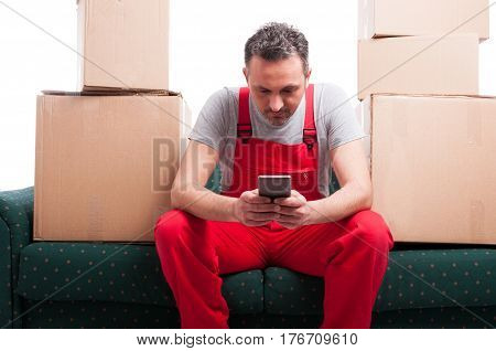 Mover Man Sitting On Couch Holding Smartphone