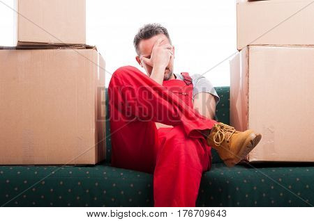 Tired Mover Man Sitting On Couch With Cardboard Boxes Around