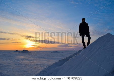 Alone young man climbing (standing) iceberg (ice mountain) and watching winter sunset. Novosibirsk Reservoir (Ob sea) Ob river Siberia Russia.