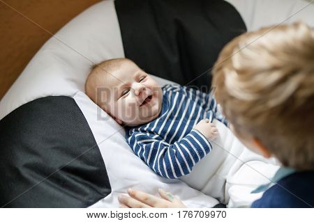 Happy little kid boy with newborn baby boy, cute brother. Siblings. Schoolchild and baby playing with colorful toys and rattles together. Kids bonding. Family of two bonding, love.