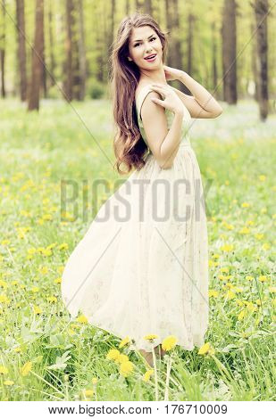 Young beautiful woman enjoying the fresh air in green forest.